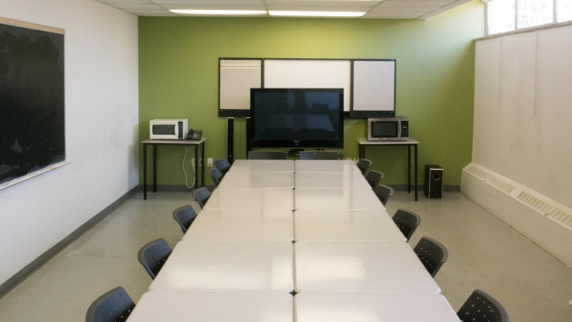 Classroom with tables, blackboard, and TV