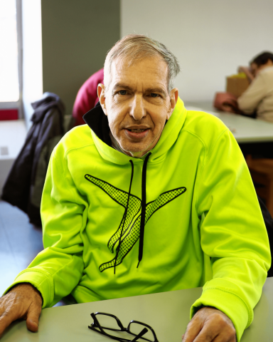 An older man is seated at a desk. He is smiling and wearing a bright sweatshirt.