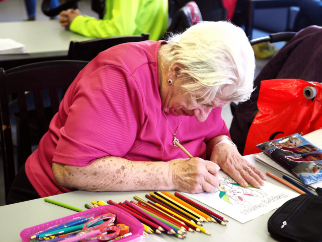 An older woman is seated at a desk colouring a picture. There are many pencil crayons on the desk beside her.