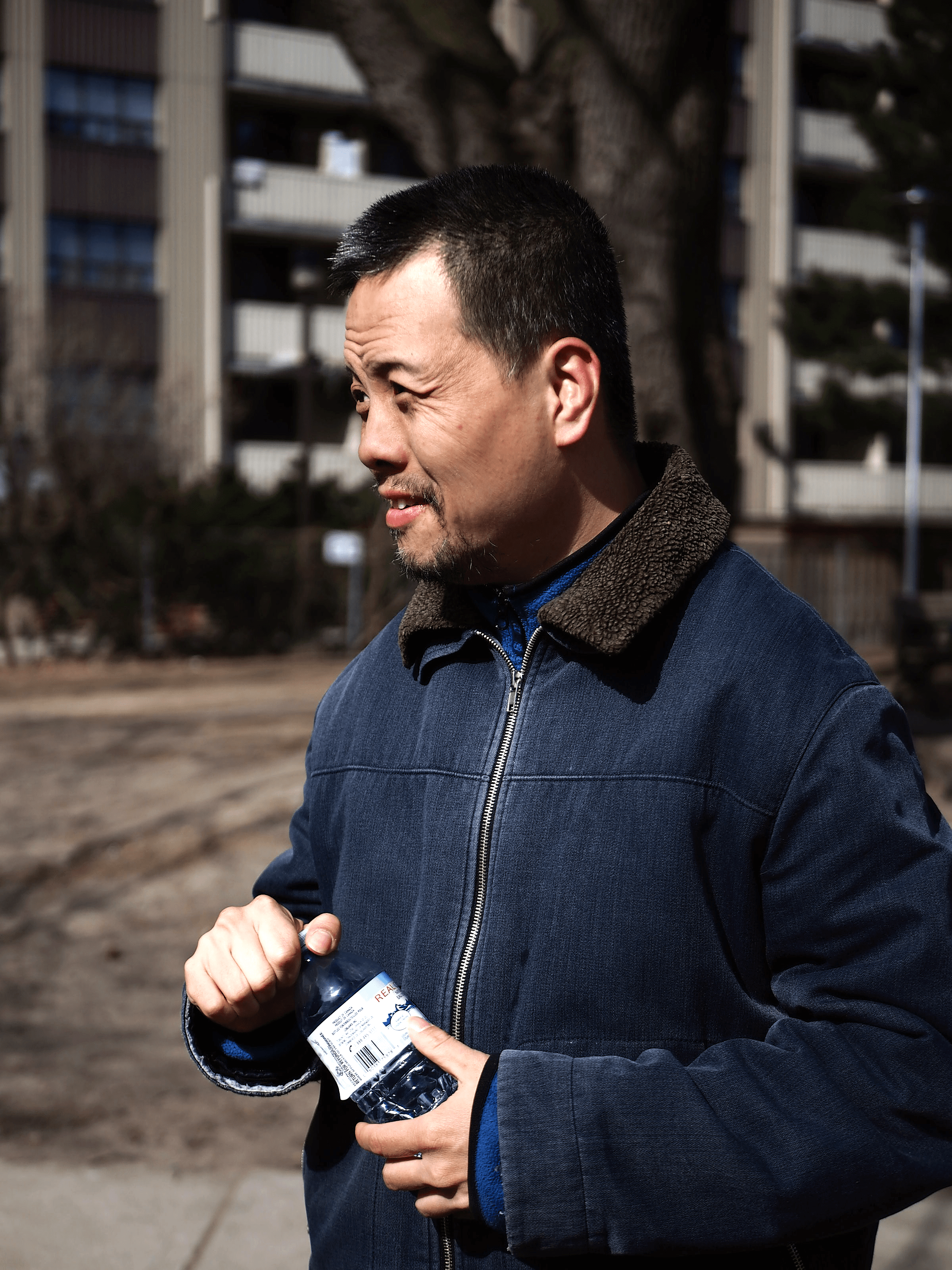 A man is standing outside and smiling. He is holding a water bottle and wearing a coat.