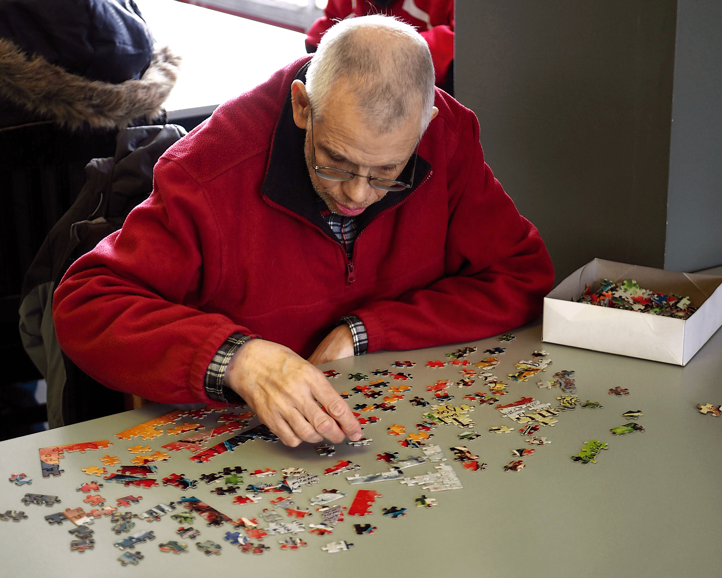 An older man is working on a puzzle.