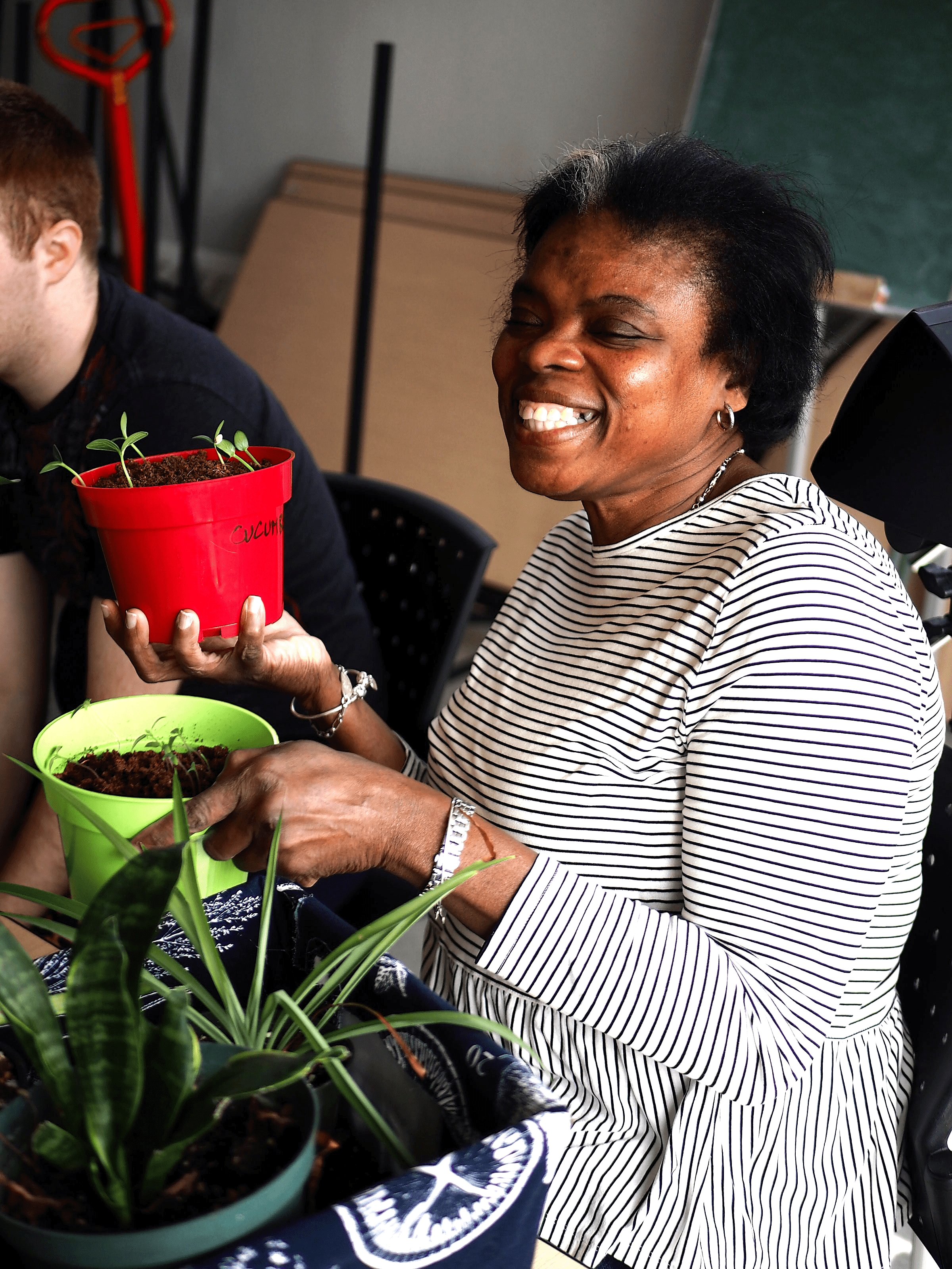 A woman is holding two potted plants and smiling. There is a third potted plant beside her.