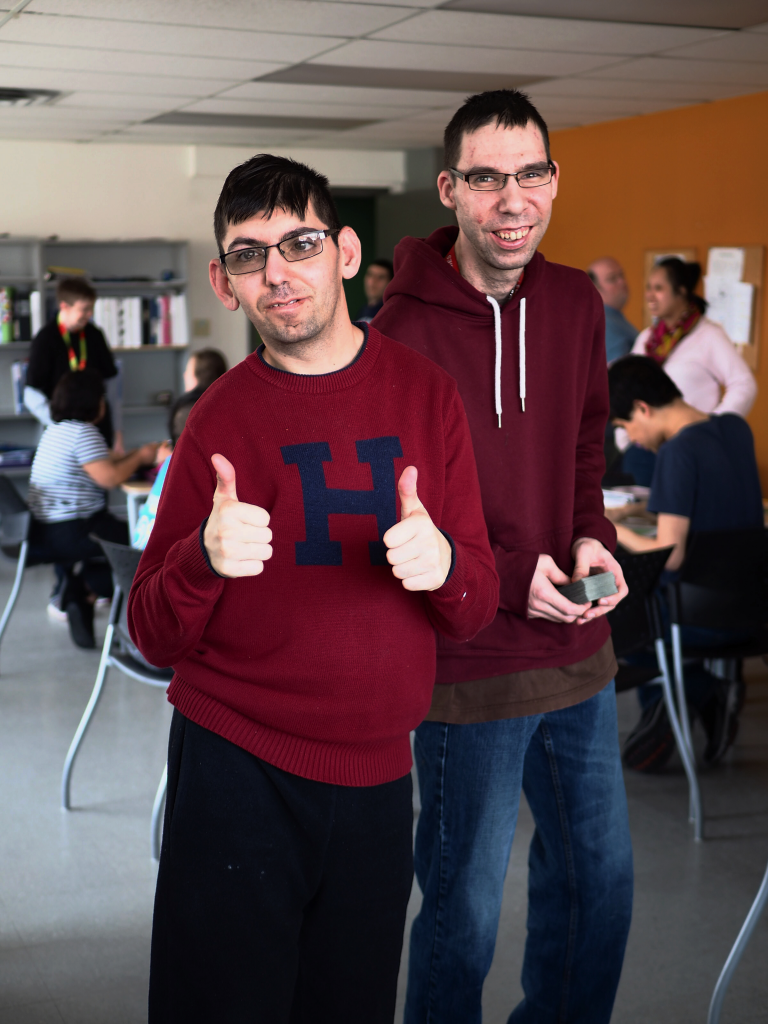 Two men are standing and smiling at the camera. One is giving the thumbs up.