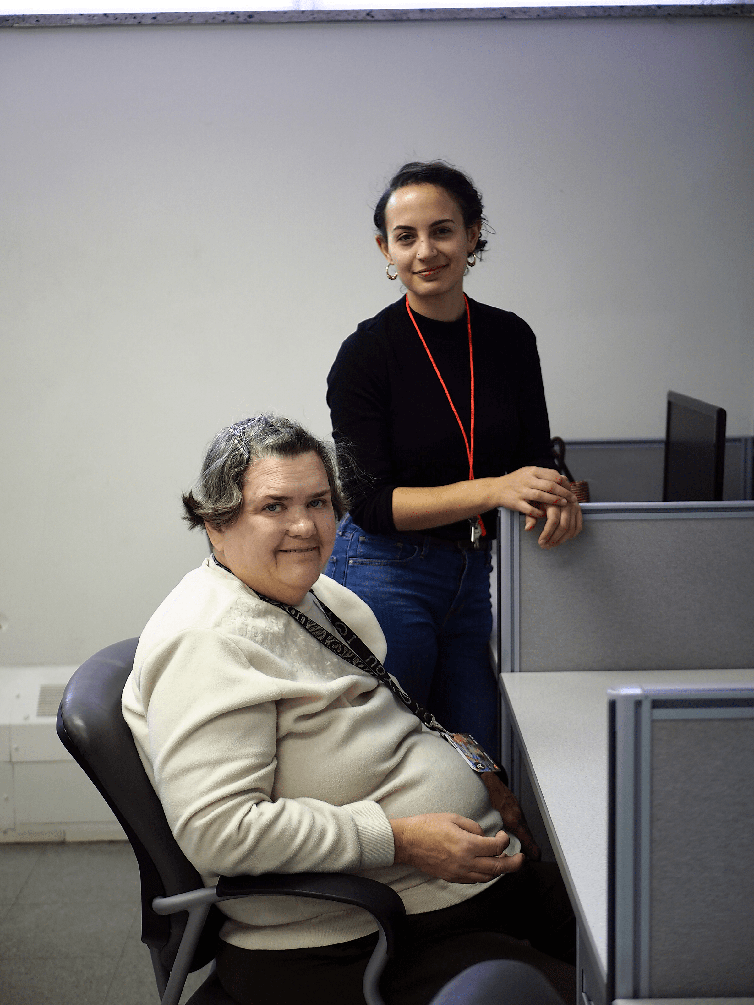 A woman is seated at a computer desk and smiling. Another woman is standing beside her.