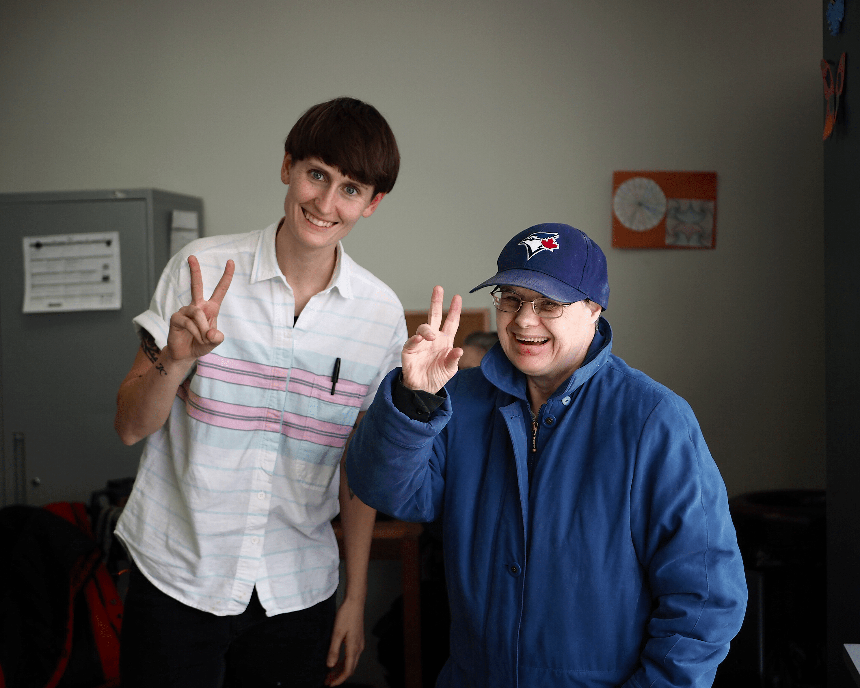 Two people are standing beside each other smiling and making peace signs.