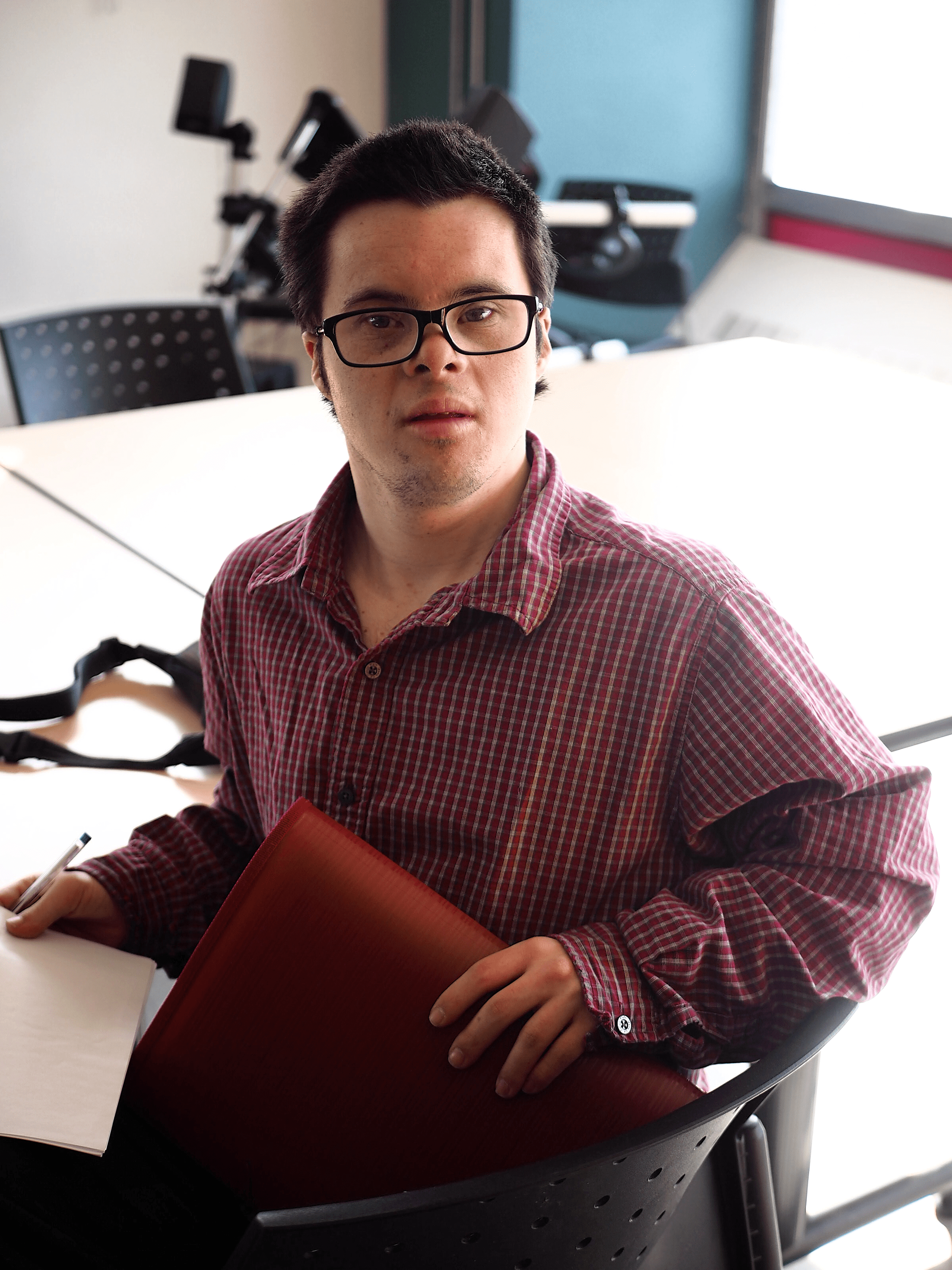 A man wearing glasses is looking at the camera. He is holding a binder.