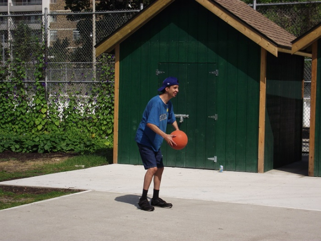 A man is outside holding a basketball. There is a green shed in the background.
