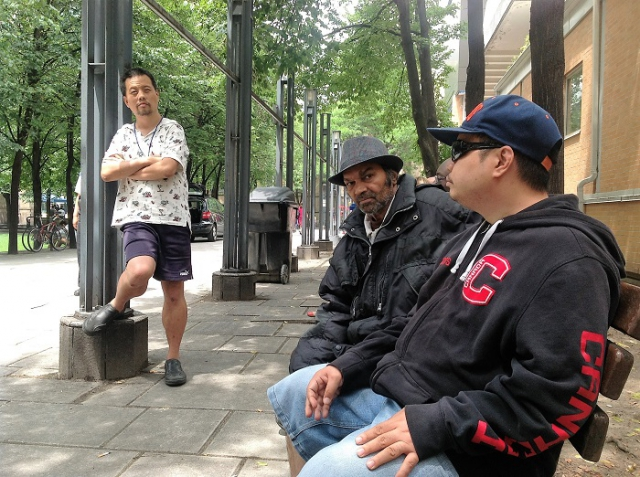 Three men are outside. Two are seated on a bench and one is standing against a column.