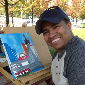A man is painting outdoors and smiling.