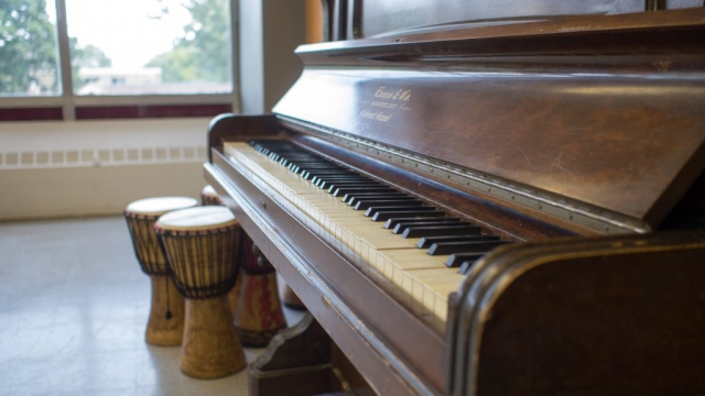 An upright piano and bongos in the Music Room